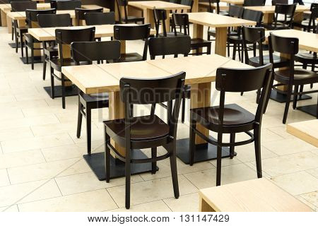 Restaurant furniture. Empty dining hall, fast food restaurant or canteen. Indoor shot with no people.