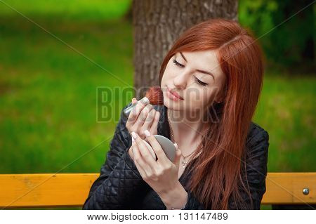 Beautiful young woman  with long red hair  in black leather jacket doing makeup using brush applying foundation powder, sitting on the bench in the park