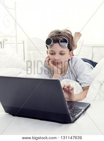 boy play with laptop indoors