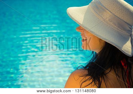 Side view portrait of a beautiful young female wearing sun hat. Swimming pool blue water surface in the background. Enjoying summer vacation concept.