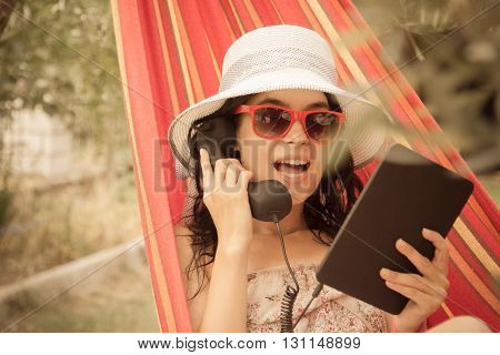 Young female having a call by using retro styled handset and tablet device while lying in hammock in the garden.