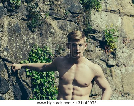 Muscular young guy with beautiful sexy body and bare torso standing outdoor on masonry wall background with vine