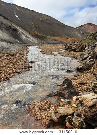 National park Landmannalaugar in Iceland. Stream to gorges between mountains of a black volcanic ash