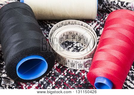 Several spools of thread of different colors and sizes with meter