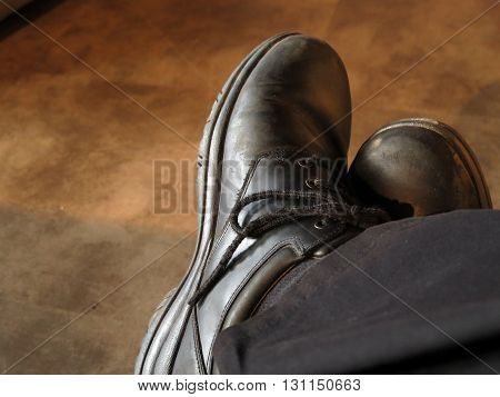 Man wearing old shoes that are photographed off center
