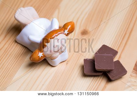 Little angel and chocolate pieces broken decorative figurine with sweet dessert on wooden background