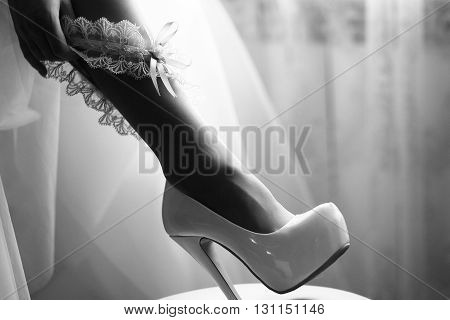 Bridal sexy leg in elegant high heel shoe with putting on beautiful ribbon wedding garter by female hand black and white