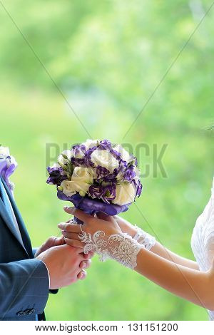 Bride and groom holding in their hands beautiful wedding bouquet of white and lilac roses flowers bridal accessory on mariage ceremony on green background