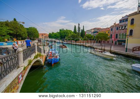 VENICE, ITALY - JUNE 18, 2015: Boats are the main transporation way on Venice, bridges in the middle for pederestians. great weather