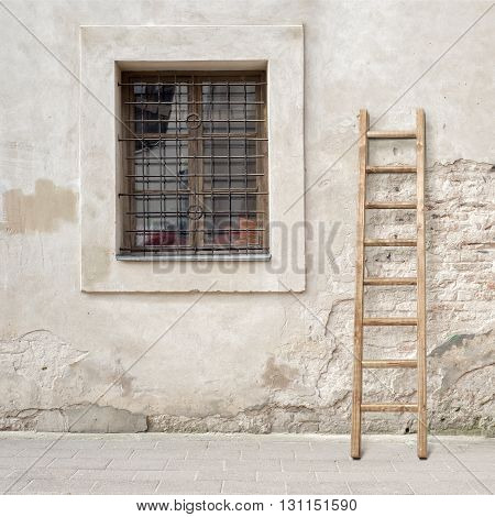 abandoned grunge cracked brick stucco wall with a window grilles and wooden ladder