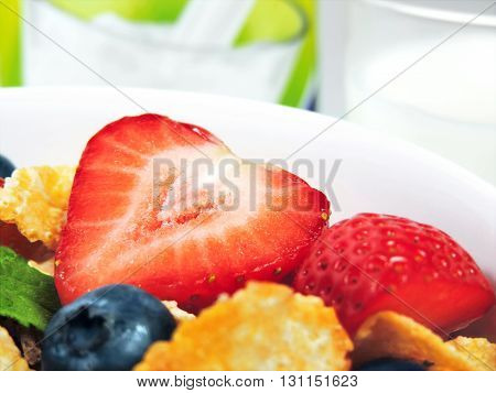 Breakfast bowl with fresh fruits and corn flakes. Close up.