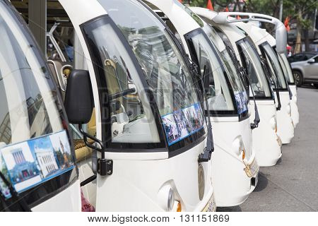 Hanoi, Vietnam - May 21, 2016: Green electric car vehicles parking in range while waiting for passenger on a 'green tour' around the old quarter street of Hanoi and Hoan Kiem (Sword) lake.