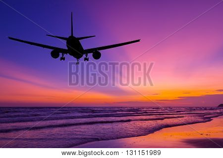 Silhouetted commercial airplane flying above the sea at sunset