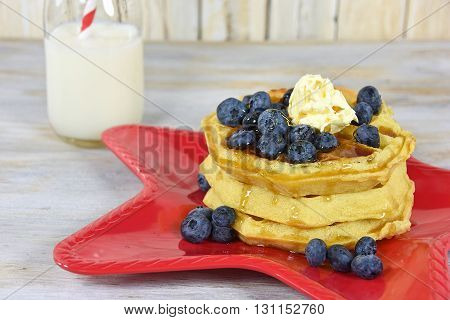 stack of waffles with butter, syrup and blueberries on red star plate