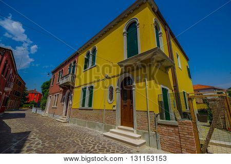 MURANO, ITALY - JUNE 16, 2015: Yellow pinturesque house at the beggining of a beautiful alley with colored houses.