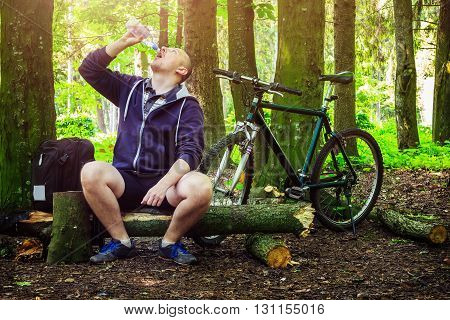 Cyclist with backpack young man drinking water from bottle in beautiful forest summertime journey