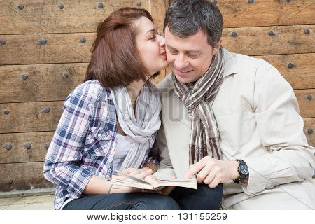 Lovely Couple Kissing And Flirting Sitting In A Bench With A Guide Of Tourism