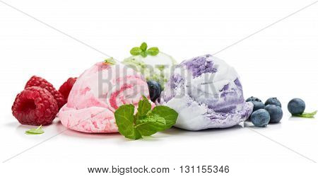 Three scoops of ice cream (blueberry raspberry kiwi) with mint leaves isolated on a white background.