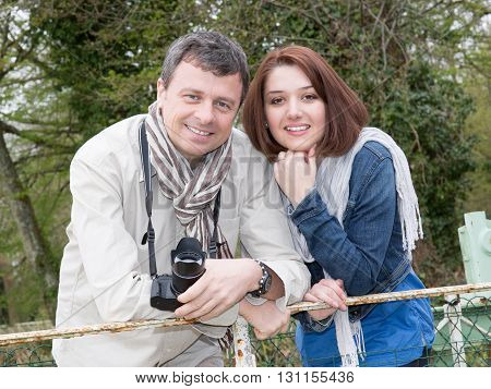Happy Couple Posing With A Camera Outside, Visiting