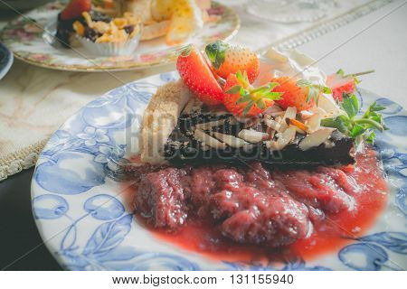 Chocolate cake with fresh strawberries and strawberry sauce(vintage effect)
