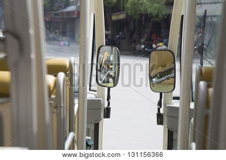 Close up of a mirror on electric car on Asia street.
