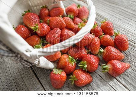 Strawberry dropped out of the basket on wooden boards.