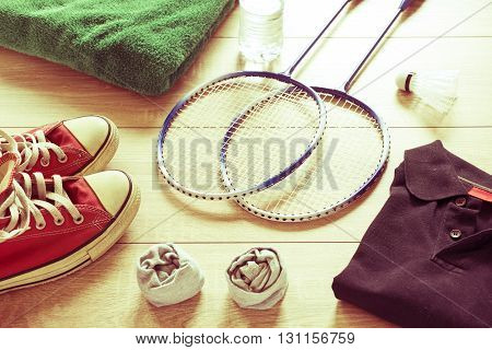 Rackets for badminton, shuttlecock, polo shirts, shoes, towel and water on a wooden floor. Retro effect,