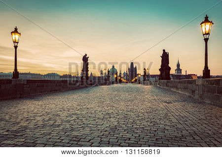 Charles Bridge at sunrise, Prague, Czech Republic. Dramatic statues and medieval towers. Unique view at dawn when there are almost no people on the bridge. Vintage