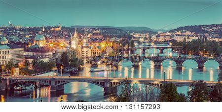 Prague, Czech Republic bridges panorama with historic Charles Bridge and Vltava river at night. Vintage