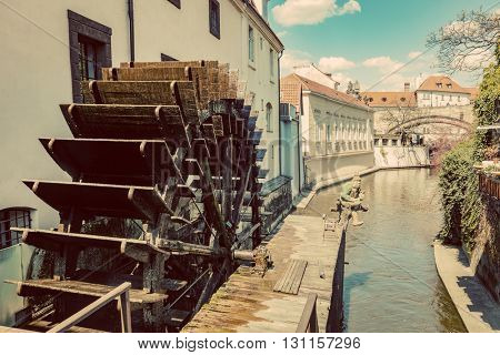 Historic water mill on Kampa Island in Prague, Czech Republic. Branch of the Vltava river, the Certovka or Devil's Stream. Vintage