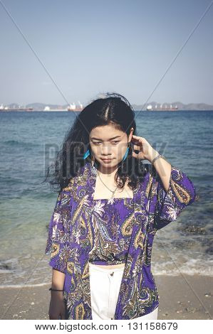 asian woman long black hair with blue shawl and white jeans on sea and blue sky blur background vintage tone