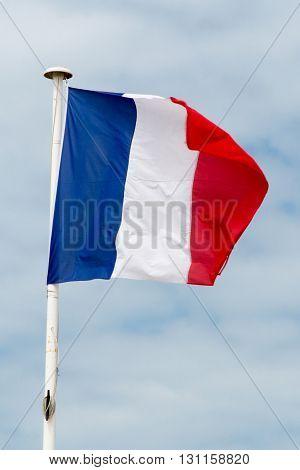 Nice French Flag Against Blue Cloudy Sky.