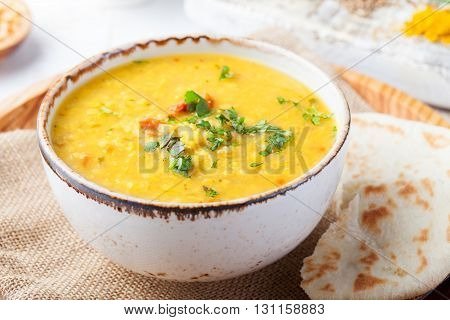 Lentil soup with pita bread in a ceramic white bowl on a wooden background