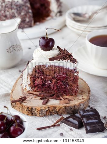 Black forest cake , decorated with whipped cream and cherries Schwarzwald pie, dark chocolate and cherry dessert on a white wooden background