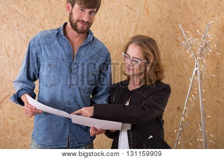 Shot of a middle-aged woman talking to a young man while showing him some papers both standing against the chipboard wall