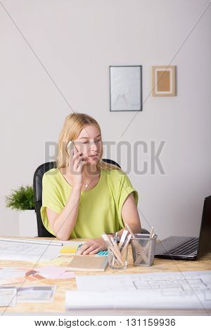 Photo of a young architect behind a desk full of papers and documents talking on the phone