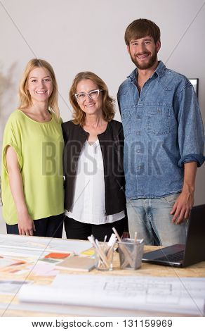 Shot of three interior designers standing behind a desk full of papers and smiling at the camera