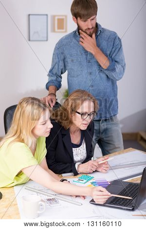 Shot of a team of architects working together at a drawing desk using a laptop