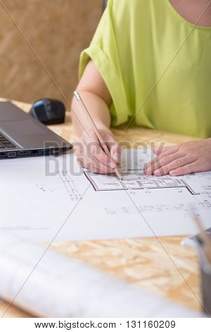 Close-up of a drawing table in an architect's office with a young woman making some corrections on a technical drawing