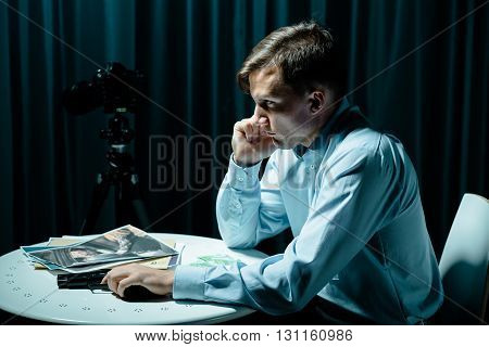 Man sitting beside table talking on cellphone pictures and gun lying on a table dark interior