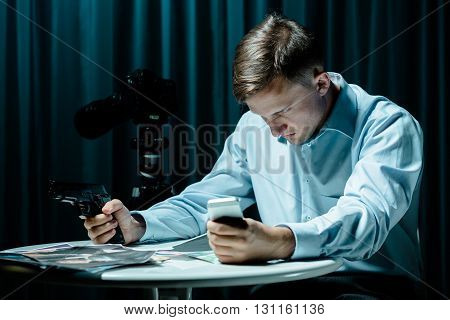 Secret agent sitting in dark interior holding gun and cellphone