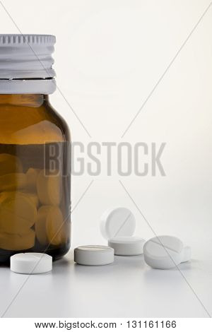 Glass pill bottle and round white pills on white background