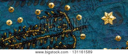 Close up detail of vintage sari fabric with gold and black embellishments.Blue background.