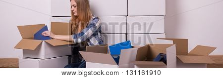 Shot of a young woman sitting on a floor and carefully packing her things into boxes