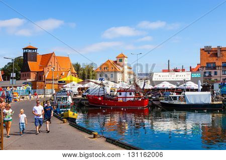 HEL, POLAND - AUGUST 10, 2015: People walking through in the port on the waterfront with many boat and sailboat in Hel. Hel is one of most famous cruise travel destinations in Poland.