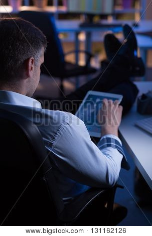 Worker sitting at night at his office using tablet