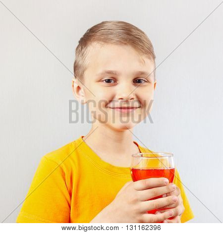 Little blonde boy with a glass of fresh red lemonade