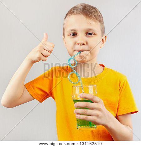 Little funny boy drinking a fresh green lemonade through a straw