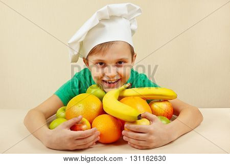 Little funny boy with fruits at the table