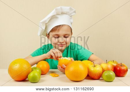 Little boy in chefs hat peeling fresh orange at the table with fruits